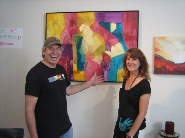"""Phil Cunningham, President, CCAS, and artist Michelle Andres in front of her work """"New Beginnings,"""" mixed media."""