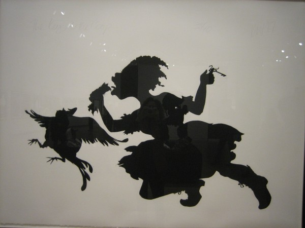 "Kara Walker, ""The Keys to the Coop,"" lino cut on paper, 1997.  According to the Crocker, ""Caught mid-run in her pursuit of the headless chicken, this raggedly dressed girl dangles keys from one hand and a holds the bird's missing head in the other.  Various racial associations are captured here - not excluding the lore of voodoo ritual - but Walker also creates a sense of empowering rebellion."
