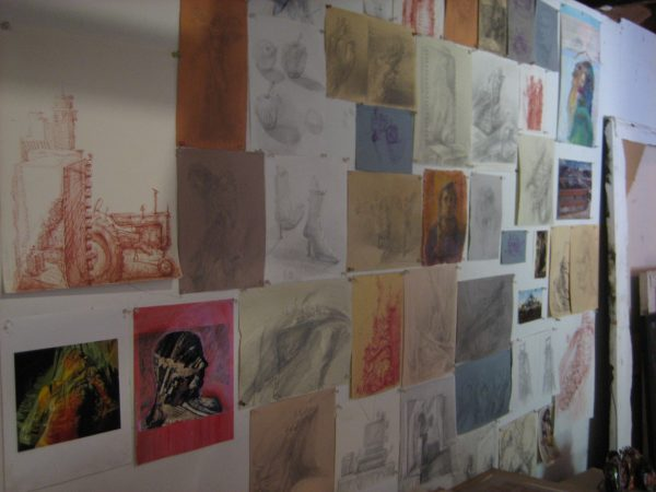 A wall of Jeff Myers' studio is line with his drawings.